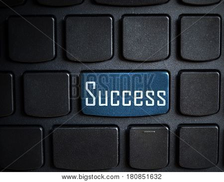 Keyboard with blue Success button - business concept background
