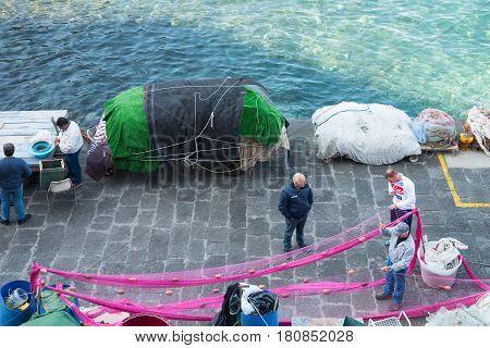 Sorrento Italy - November 15 2015: Fishermen working with the nets in Marina Grande