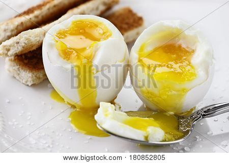 Two soft boiled eggs with toast soldiers over a white plate. Extreme shallow depth of field with selective focus.