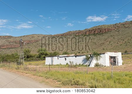 NIEU BETHESDA SOUTH AFRICA - MARCH 22 2017: An old barn and windmill near Nieu-Bethesda an historic village in the Eastern Cape Province