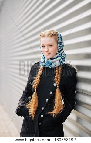 Young beautiful fashionable redhead woman with braids hairdo in blue white headcraft stylish denim black trench jacket posing outdoors against urban style background of metal strips