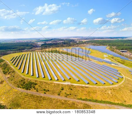 Aerial view to solar power plant in agricultural landscape. Industrial background on renewable resources theme. Industry of power and fuel generation in European Union.