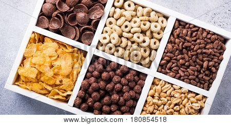 Variety of cold quick breakfast cereals in white wooden box, healthy eating for kids, overhead shot