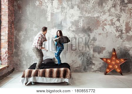 Young couple fighting pillows in the loft style bedroom.