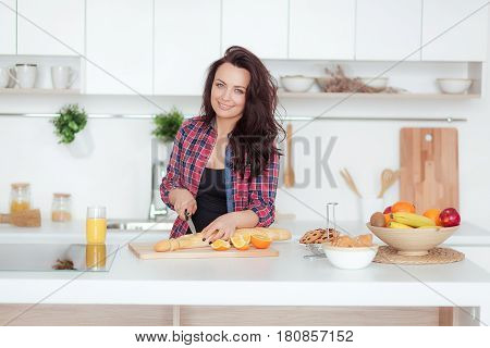 Happy beautiful young womancuts a baguette on the kithen.