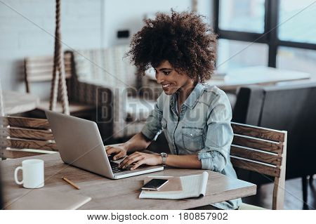 Her job is her life. Beautiful young African woman using computer and smiling while sitting at her working place in cafe