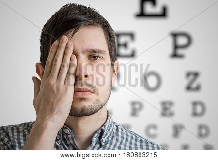 Young Man Is Covering His Face With Hand And Checking His Vision