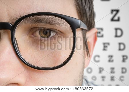 Man With Glasses Is Testing His Sight. Closeup View On Eye.