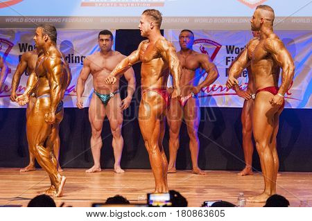 MAASTRICHT THE NETHERLANDS - OCTOBER 25 2015: Male bodybuilders flex their muscles and shows their best side pose on stage at the World Grandprix Bodybuilding and Fitness of the WBBF-WFF