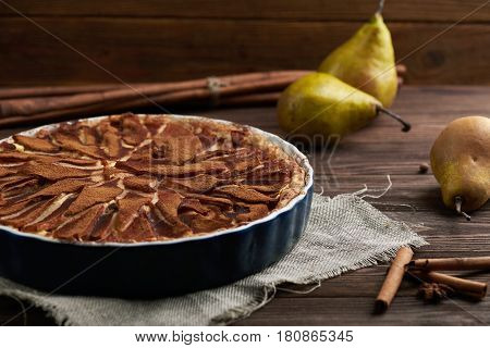 Fresh pear pie decorated with cinnamon, fresh pears and spices on a wooden background