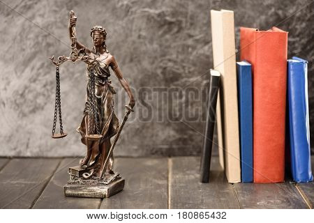 Close-up view of antique statue of lady justice and book. Law concept