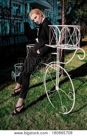 Portrait of stylish fashionable beautiful blonde woman in man black suit with bow tie outdoor nearly bicycle