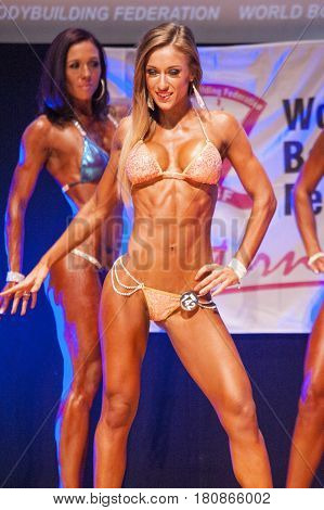 MAASTRICHT THE NETHERLANDS - OCTOBER 25 2015: Female fitness bikini model shows her best front pose at championship on stageat the World Grandprix Bodybuilding and Fitness of the WBBF-WFF
