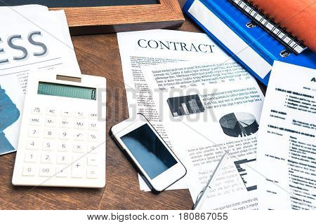 Contract Documents, Smartphone, Calculator And Business Items On Wooden Tabletop