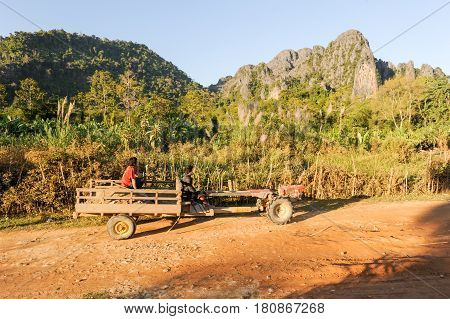 People Traveling In A Tractor Near The Village Of Vang Vien