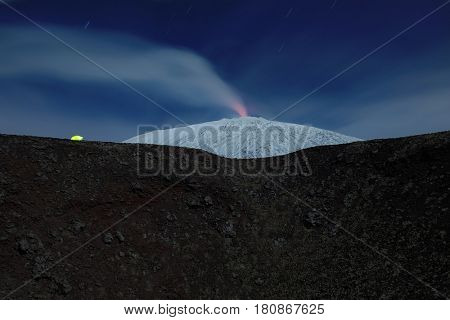 illuminated tent on the edge of an old crater in front of snowy Etna that emit volcanic steam, Etna Park - Sicily