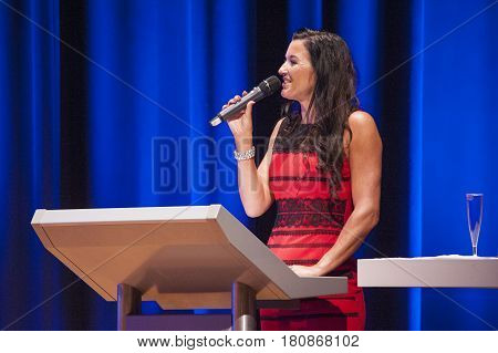 MAASTRICHT THE NETHERLANDS - OCTOBER 25 2015: Master of ceremonies behind pulpit addresses theatre crowd with microphone at the World Grandprix Bodybuilding and Fitness of the WBBF-WFF