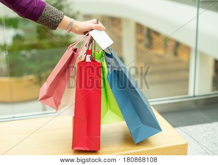Crop female hand holding colorful paper bags and platic card on background of shopping center.
