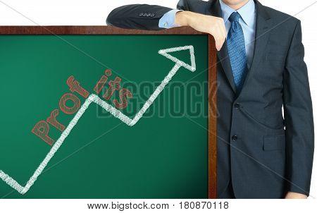 Profits on blackboard presenting by businessman or teacher
