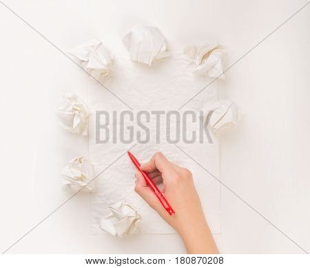 Female hand trying to write next to a few crumpled paper balls