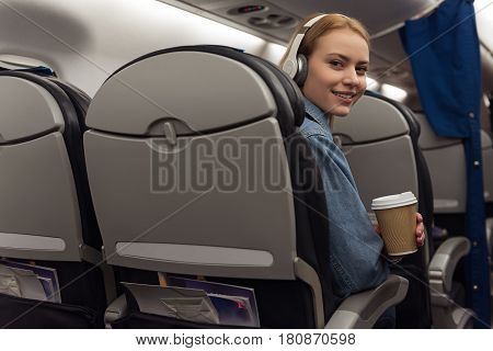 Music and good coffee always with me. Female expressing gladness . She listening music and drinking coffee. She flying by aircraft