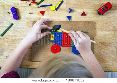 Boy playing with blocks and nails on a table. Top view.