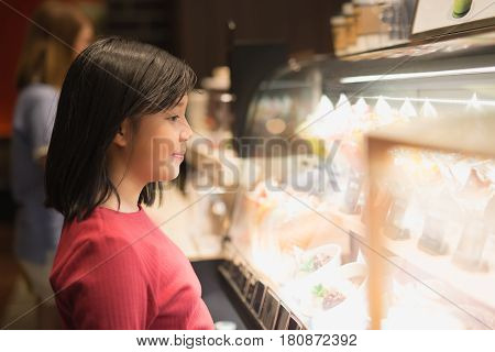 Asian girl choosing ice-cream in the glass case