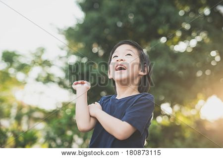Cute Asian boy looking up outdoors on summer day