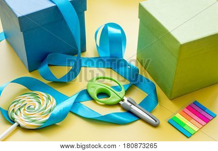 wrapping gifts in box for Mothers Day on yellow background.