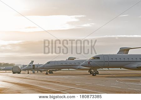 Passenger planes situating near each other on take-off runway at dawn