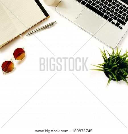 Modern home workspace with bright sunglasses, laptop keyboard, green office plant and notebook. White background, top view, flat lay
