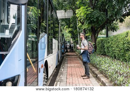 Full length side view of a young male tourist waiting for the bus in the station for public transport in Jakarta