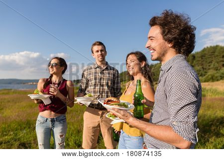 Friends at barbecue party in nature drinking beer and eating hamburger sandwiches