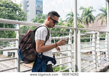 Young tourist using the mobile phone for communication or useful online information while walking on a pedestrian bridge in Indonesia