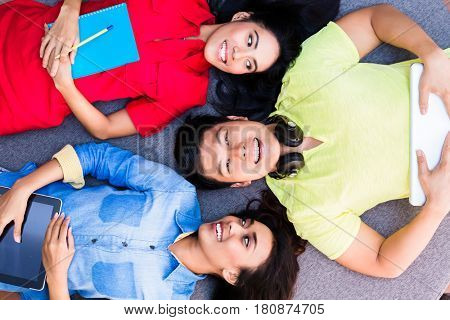 High angle view portrait of three funny young employees or students lying down on the floor at work or at the university