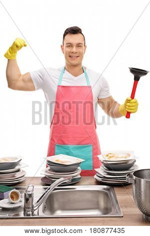 Young guy behind a sink flexing his bicep and holding a plunger isolated on white background
