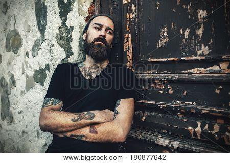 Portrait of brutal bearded man wearing blank t-shirt on the dor
