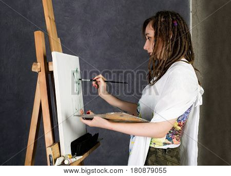 paint artist posing next to a easel and paints on an canvas, depicts a reverie. An empty easel, there is a palette on it