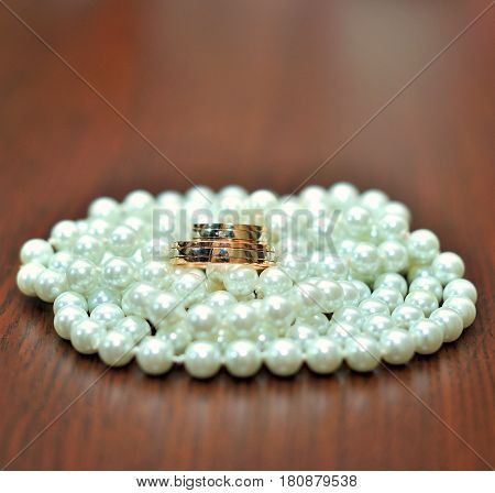 Close-up of wedding rings on wooden background
