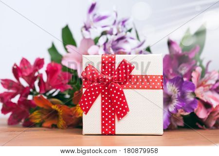 Gift box with spring flowers on wooden table. white background
