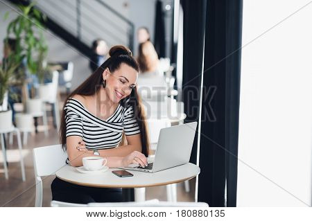 Image of happy woman using laptop while sitting at cafe. Young woman sitting in a cafe and talking with friends through the internet
