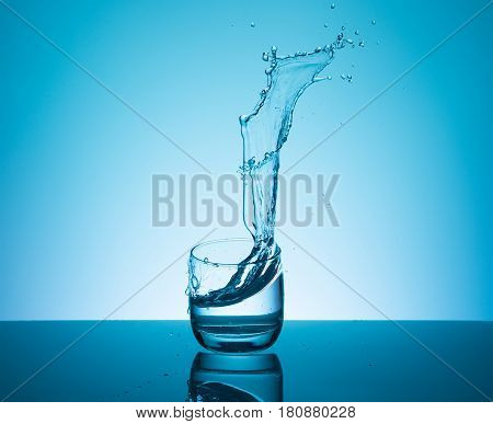 Creative splashing water in the glass on blue background.