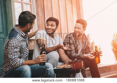 Smiling Young Friends Drinking Beer And Talking While Making Barbecue