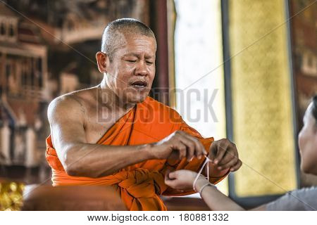 Bangkog Thailand March 4 2016: Monk tieding up a holy thread on a hand in the temple.