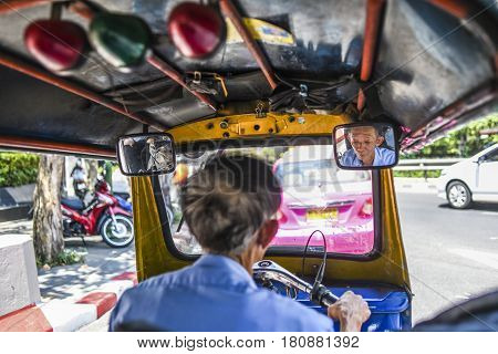 Bangkok Thailand March 3 2016: Tuk tuk old driver driving thru Bangkok with face in inside car mirror. Thailand