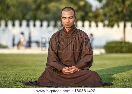 Bangkok Thailand March 4 2016: Young monk meditating in the park sitting on a grass.