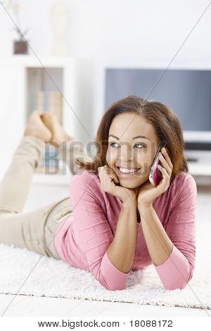 Lachend afroamerikanische Mädchen sprechen auf Handy, auf Boden zu Hause liegen.?