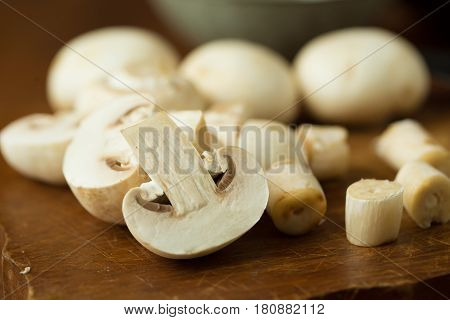 Champignon mushrooms on the wooden table. Selective focus.