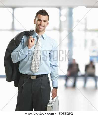 Smiling businessman standing in lobby with suitcase, leaving office.?