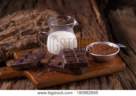 Cold Chocolate Milk Drink And Chocolate Bar On Wooden Background